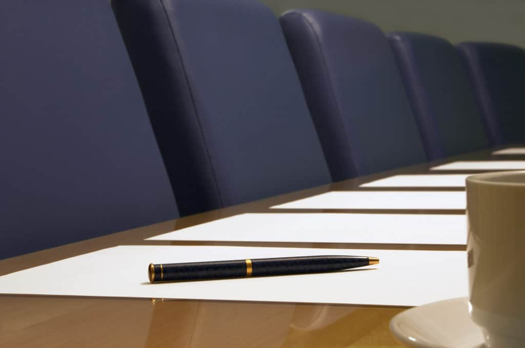 A close-up of a conference room showing a row of chairs, a table, part of a coffee cup, documents (blank) and a pen resting on a piece of paper. Sharp focus on the pen.
